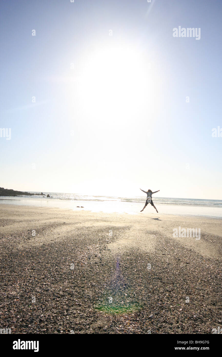 A female dancing on the beach doing star jumps. - Stock Image