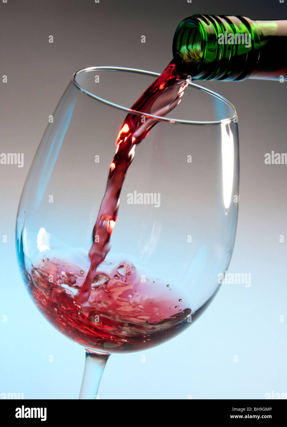 Pouring red wine into a glass - Stock Image