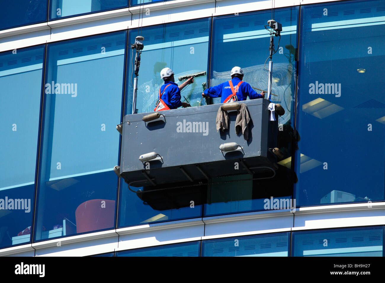 Window Cleaners Suspended In A Cradle Washing Glass