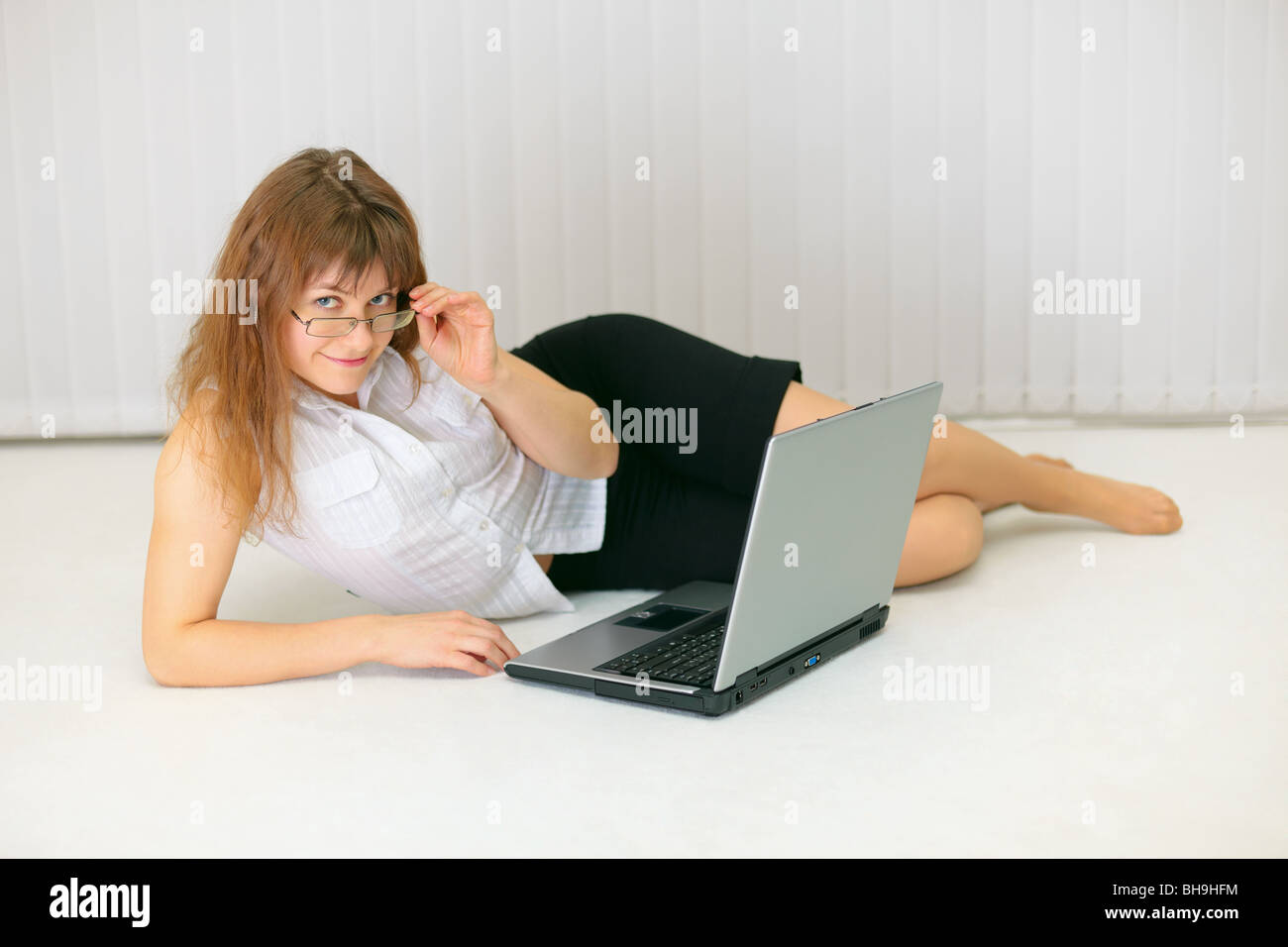 Beautiful young woman with laptop lying on the floor Stock Photo