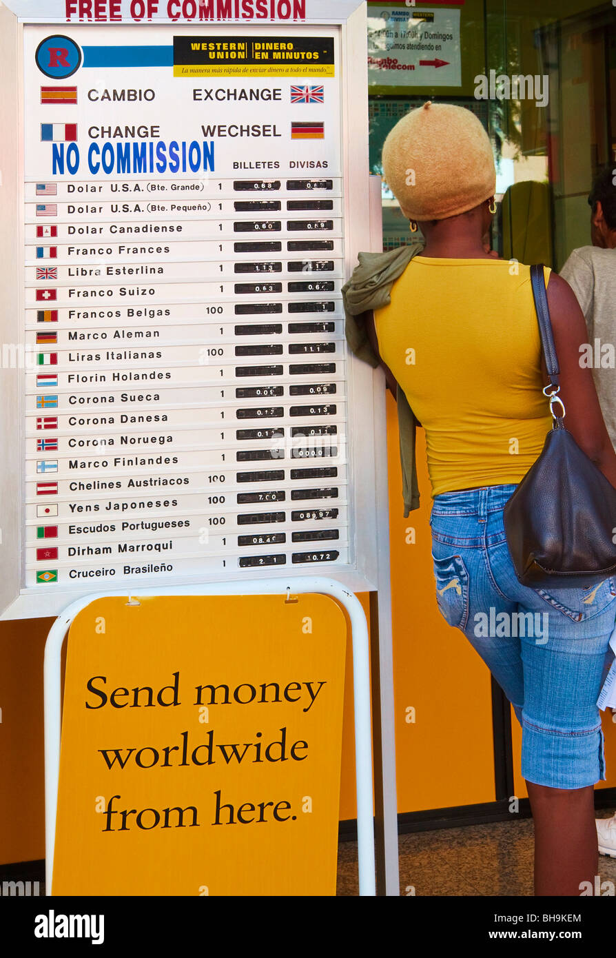 Woman leaning against international currency exchange rate board outside Western Union office in Fuengirola, Spain Stock Photo