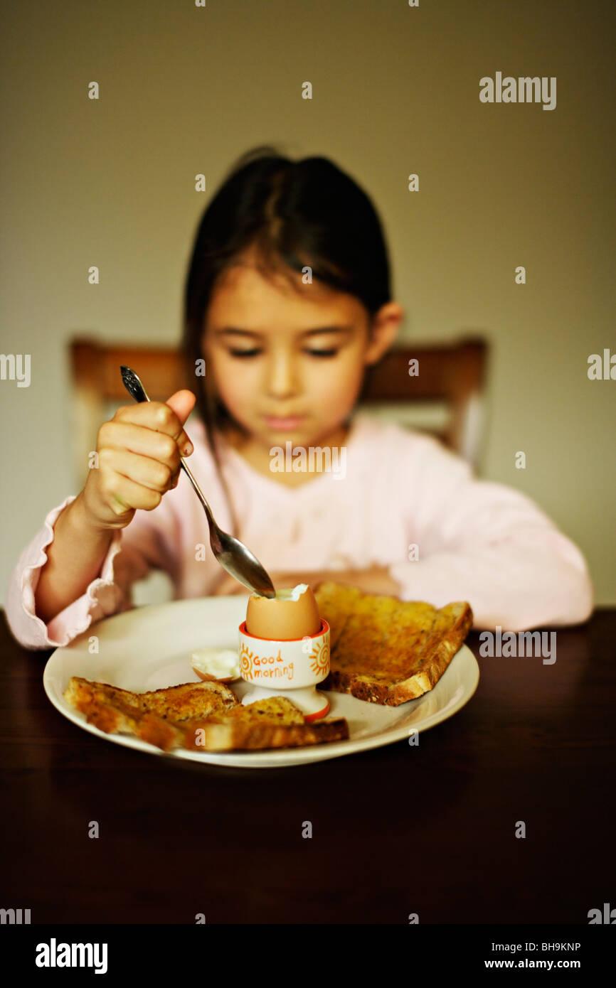 Five year old girl eats boiled egg for breakfast - Stock Image