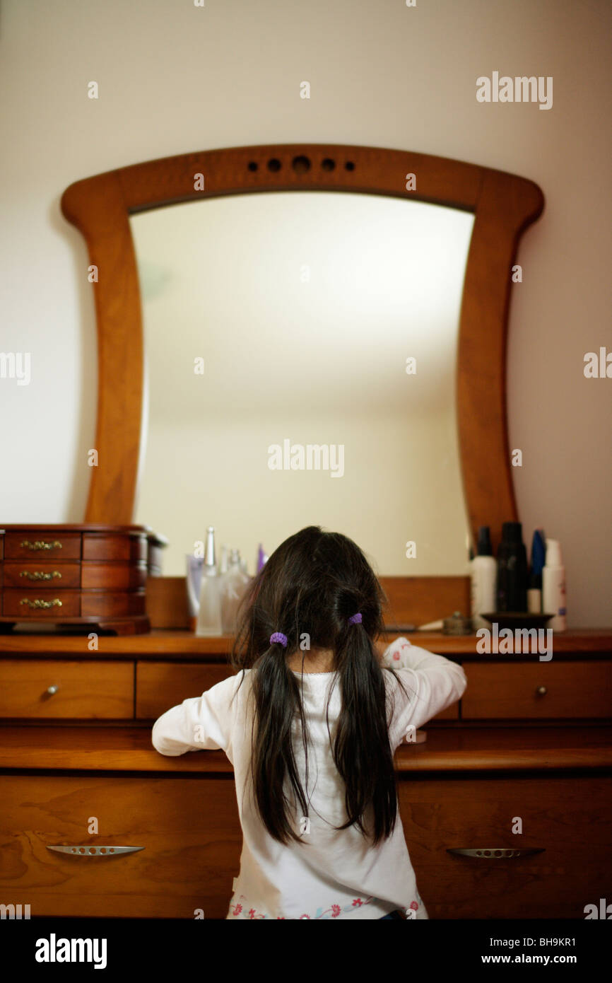 Six year old girl looks at the things on her mother's dresser - Stock Image