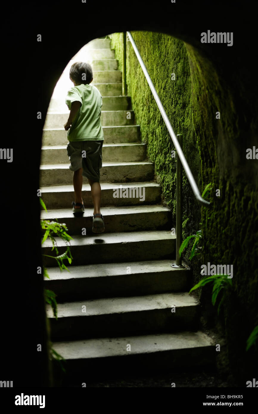 Boy runs up steps at end of garden tunnel - Stock Image