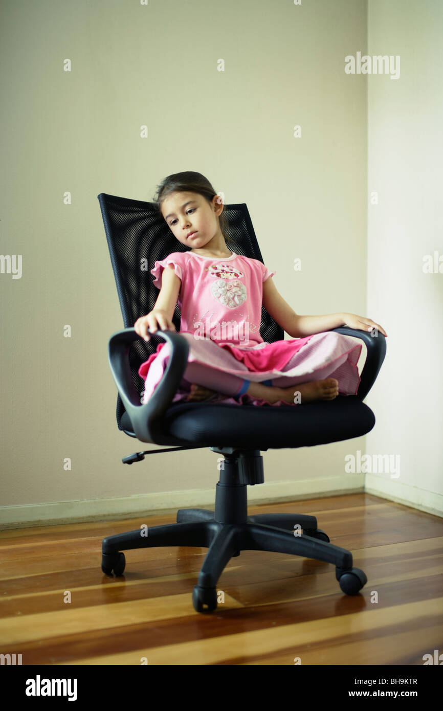 Girl contemplates in swivel chair - Stock Image