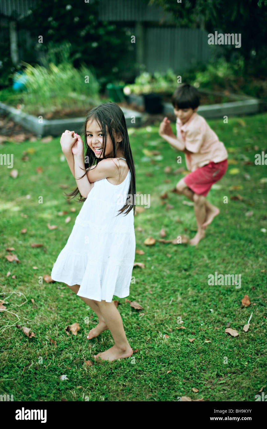 Boy and girl practice yoga in a garden - Stock Image