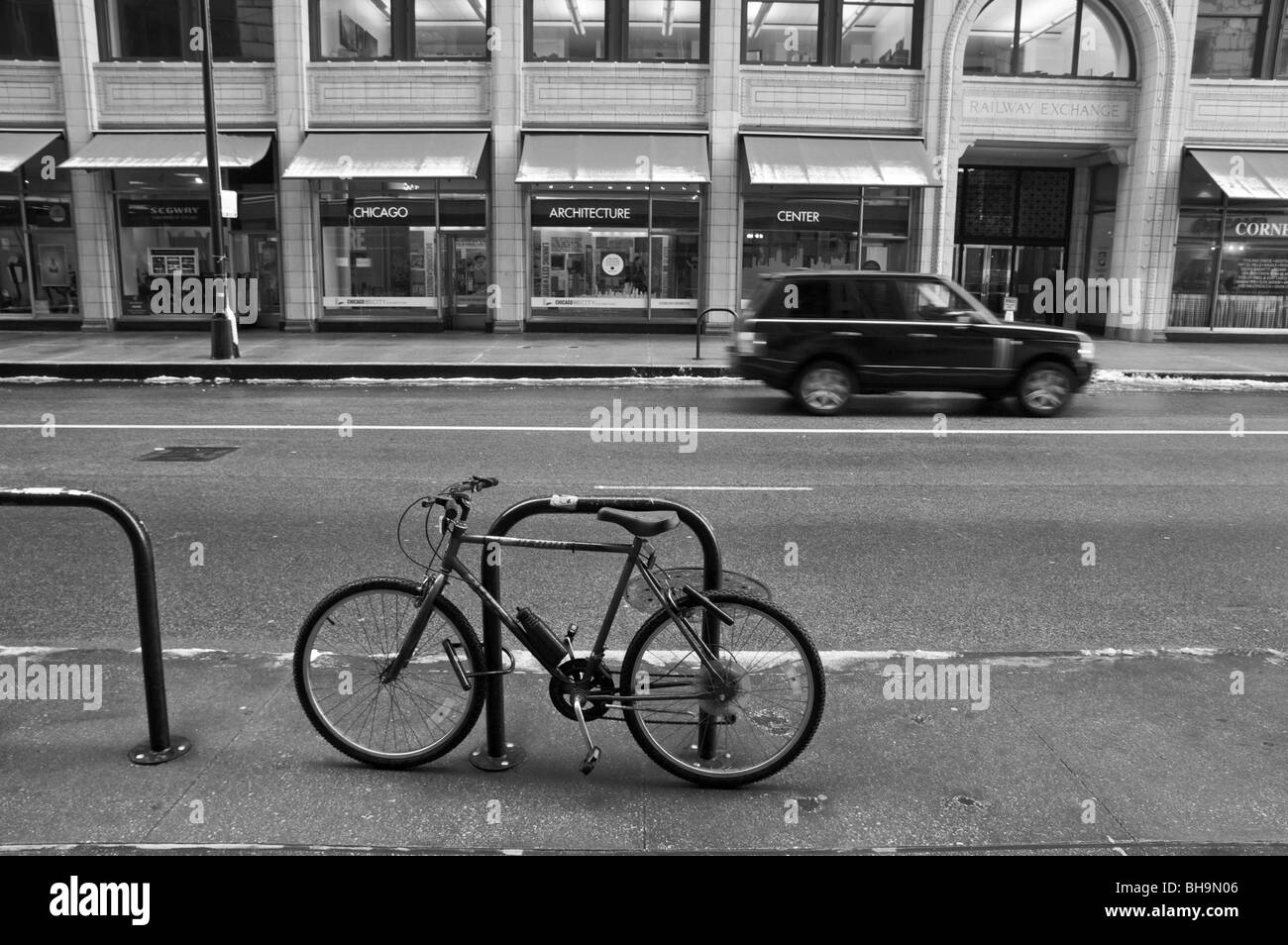 Bicycle locked to bike stand on Jackson Blvd. Chicago, Illinois. Santa Fe Building. Black and white. - Stock Image