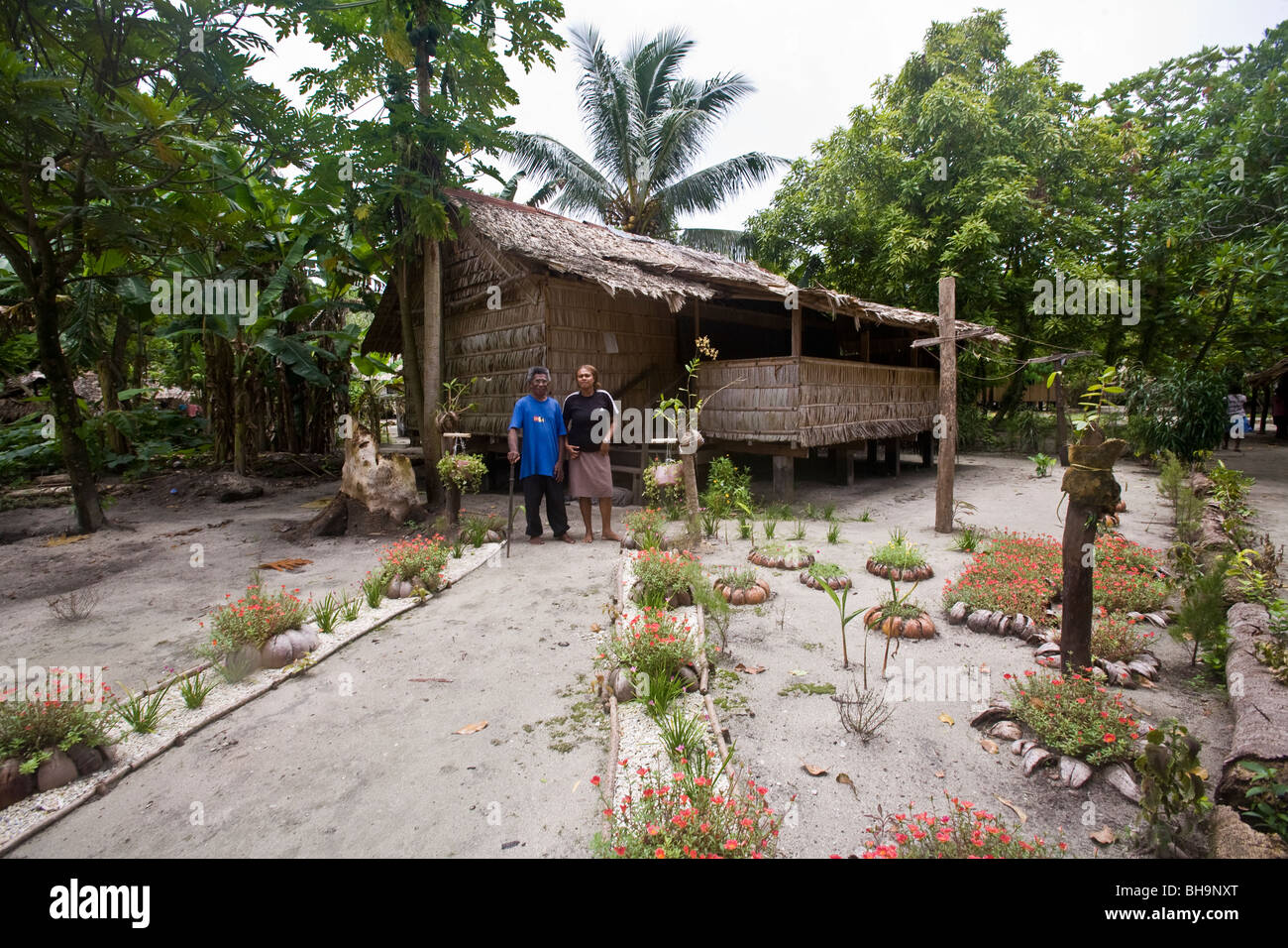 Two men stand in front of a handmade thatch hut Santa Ana Island Soloman Islands - Stock Image