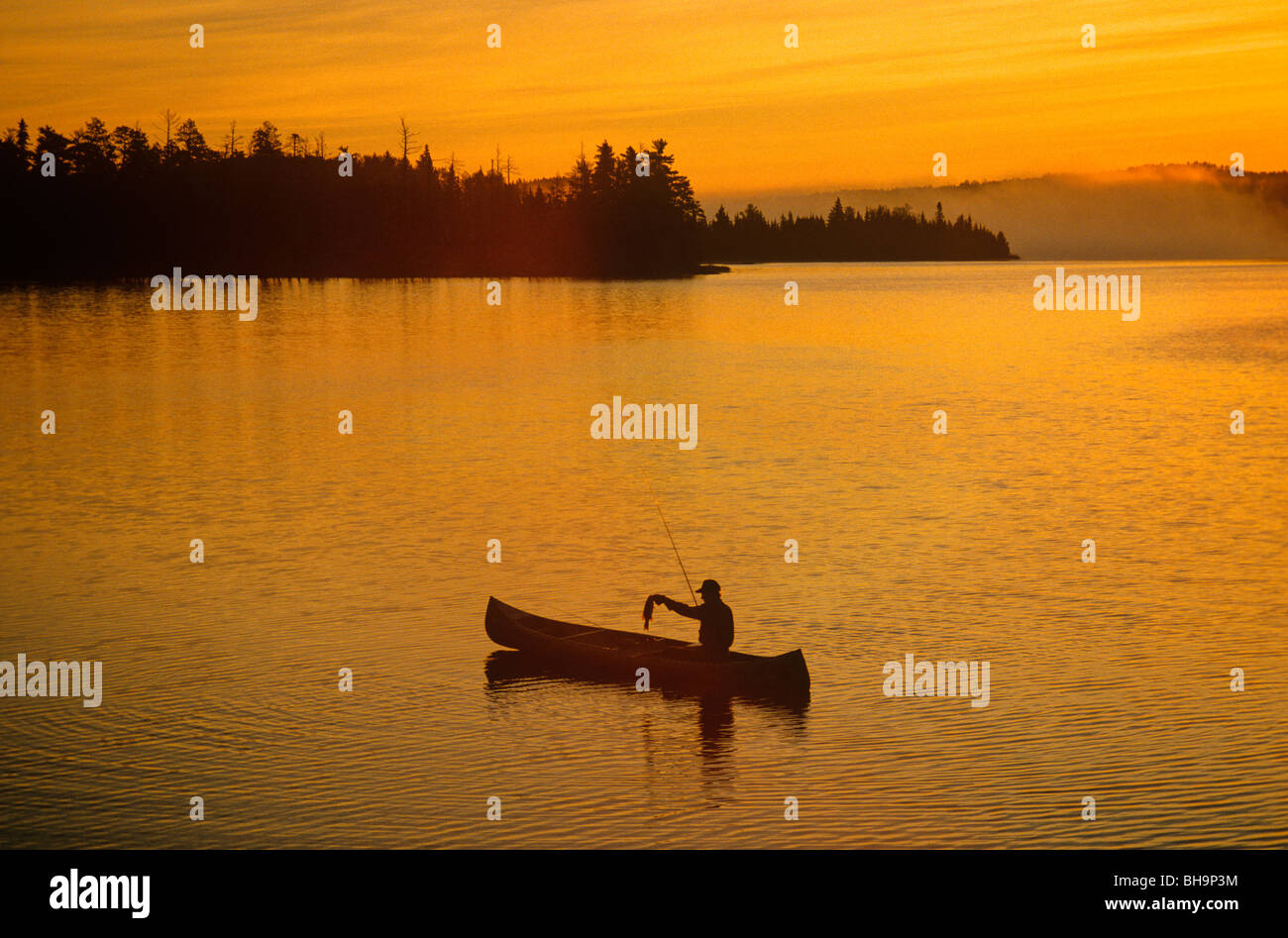 Fishing at sunrise, Boundary Waters Canoe Area lake, border of Minnesota and Ontario, Canada, USA, - Stock Image