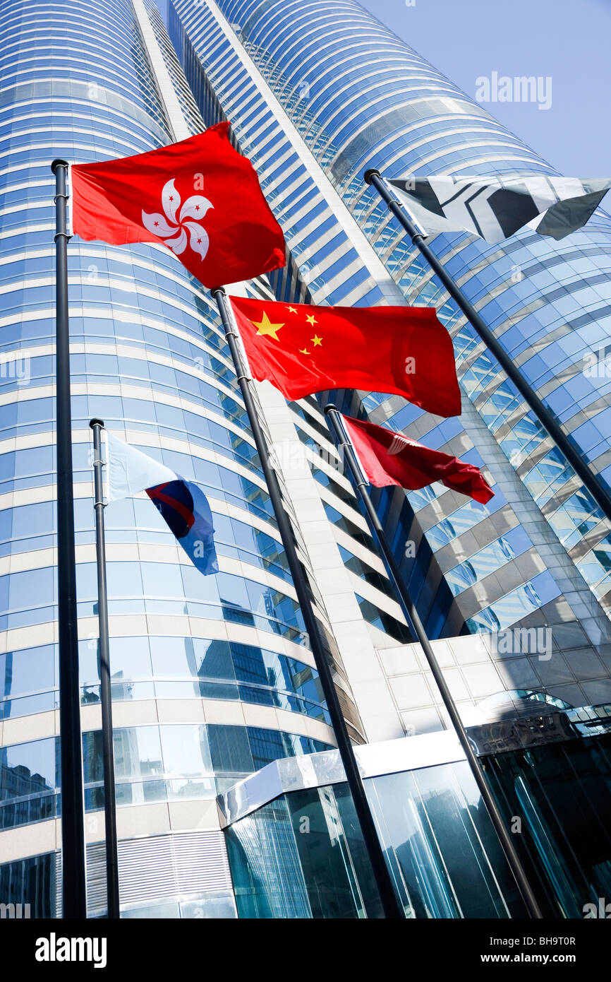 The Hong Kong and Peoples Republic of China's flags flying outside Exchange Square in Central, Hong Kong. - Stock Image