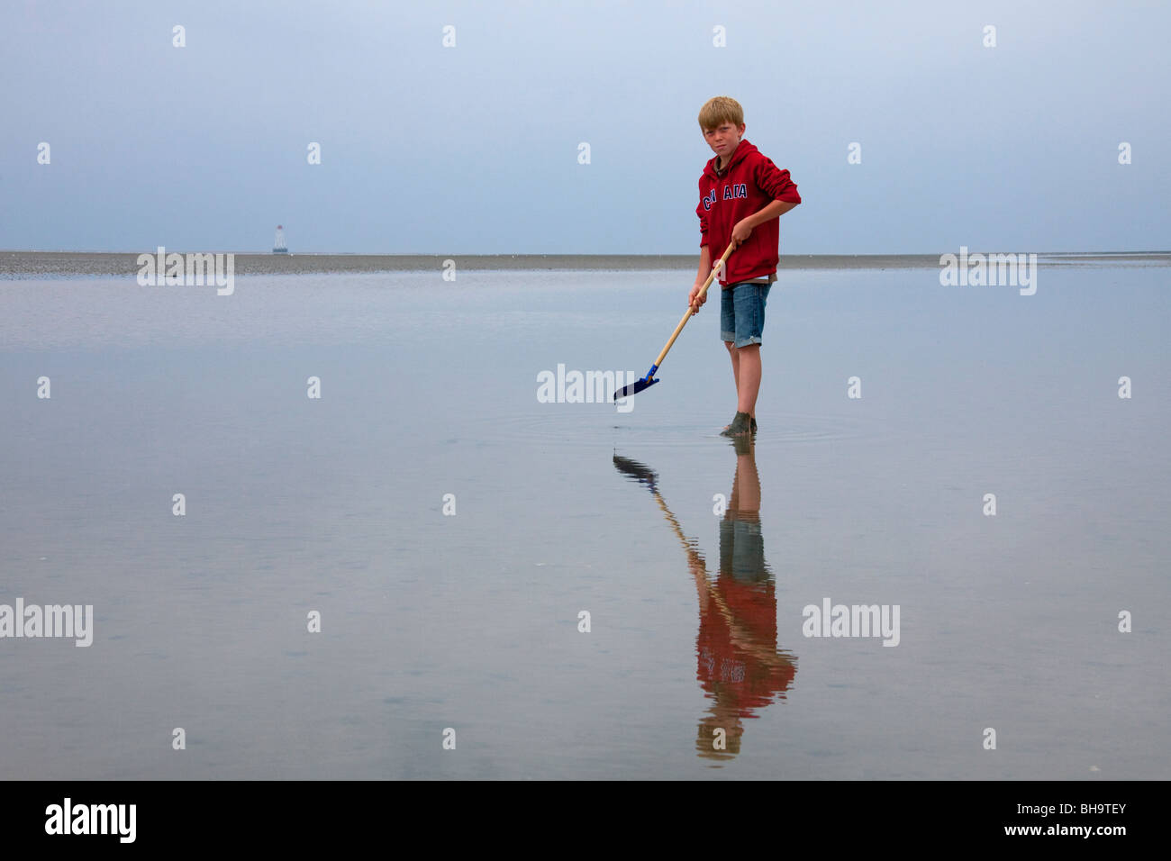 Boy with spade looking for worms on the beach at the Wadden Sea, Germany - Stock Image