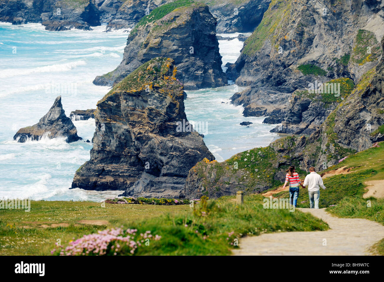 Young couple walking north along South West Coast Path north of Newquay toward sea stacks of Bedruthan Steps, Cornwall, - Stock Image