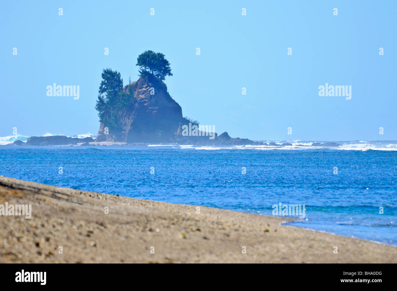 Rock formation offshore from an undiscovered tropical beach, with ocean waves - Stock Image