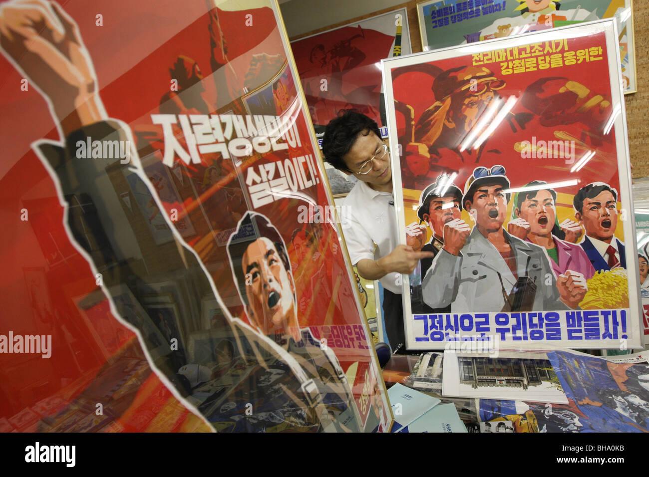 Jun Miyagawa, of Rainbow Trading Company ( a North Korean speciality bookstore) shows off North Korean products - Stock Image