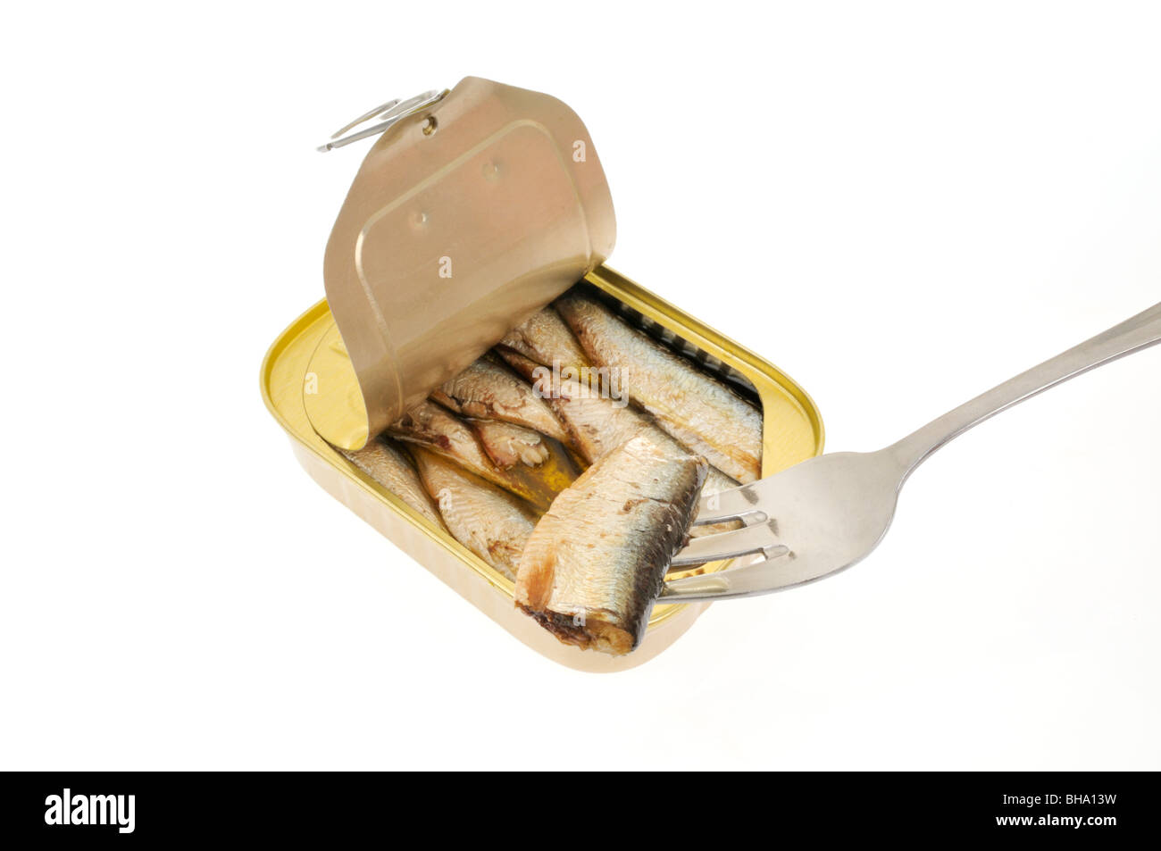 An open pull tab tin of sardines packed in oil on white background with a sardine on fork. - Stock Image