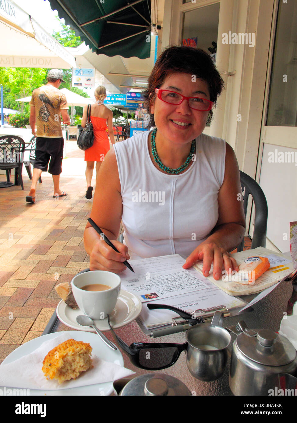 Woman writing postcards on holiday at Airlie Beach in Queensland - Stock Image