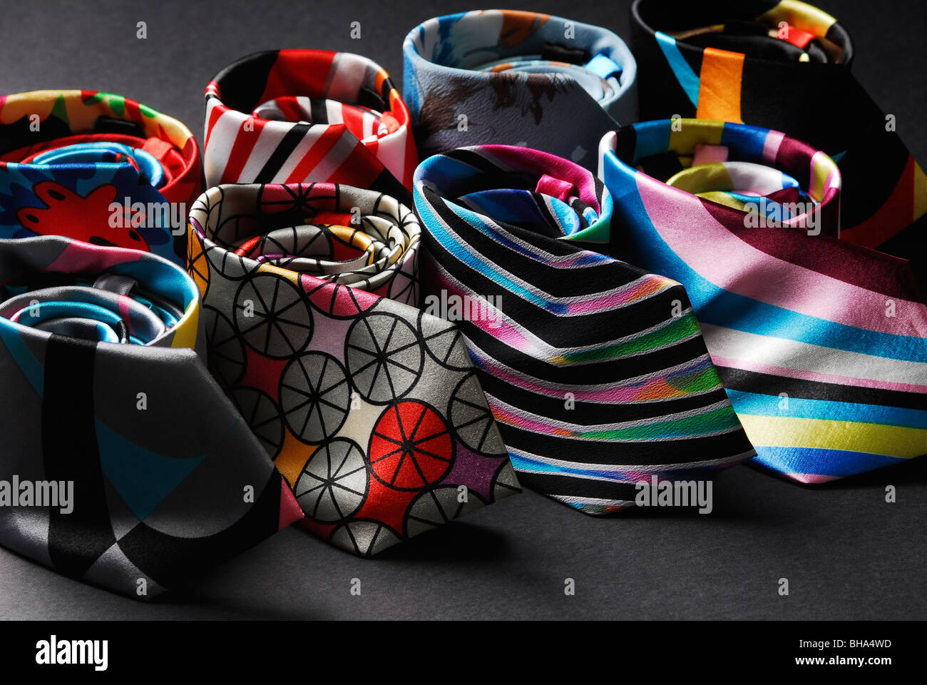 Six fancy silk ties on a black background UK - Stock Image