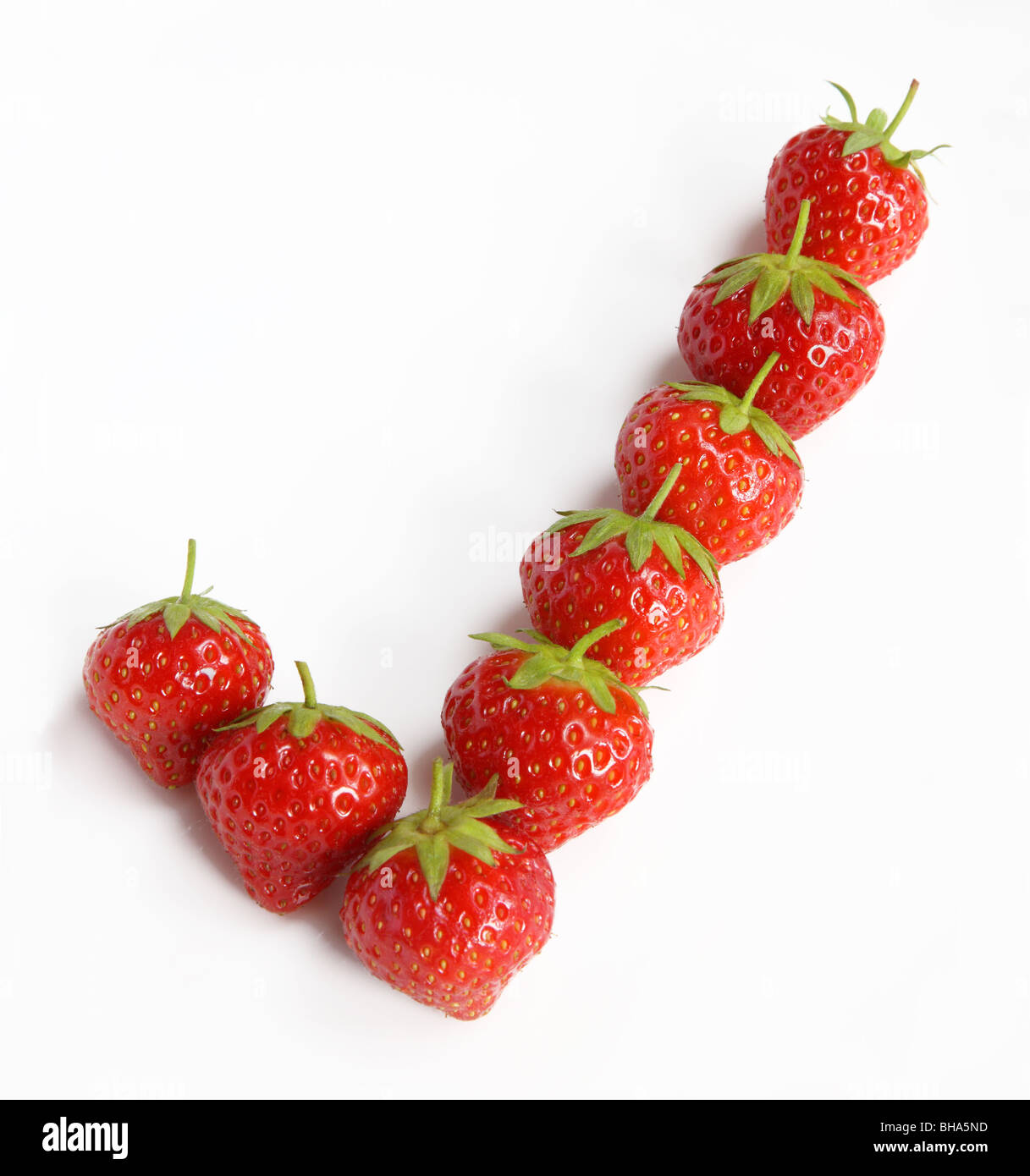 Eight ripe, fresh strawberries placed to create a tick or check. - Stock Image
