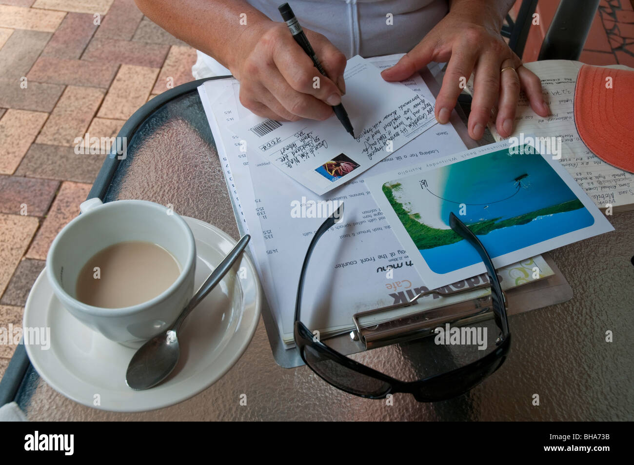 Woman writing postcards on holiday at Airlie Beach in Queensland Stock Photo