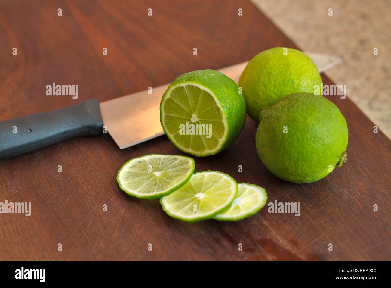 Cutting fresh limes on a chopping board - Stock Image