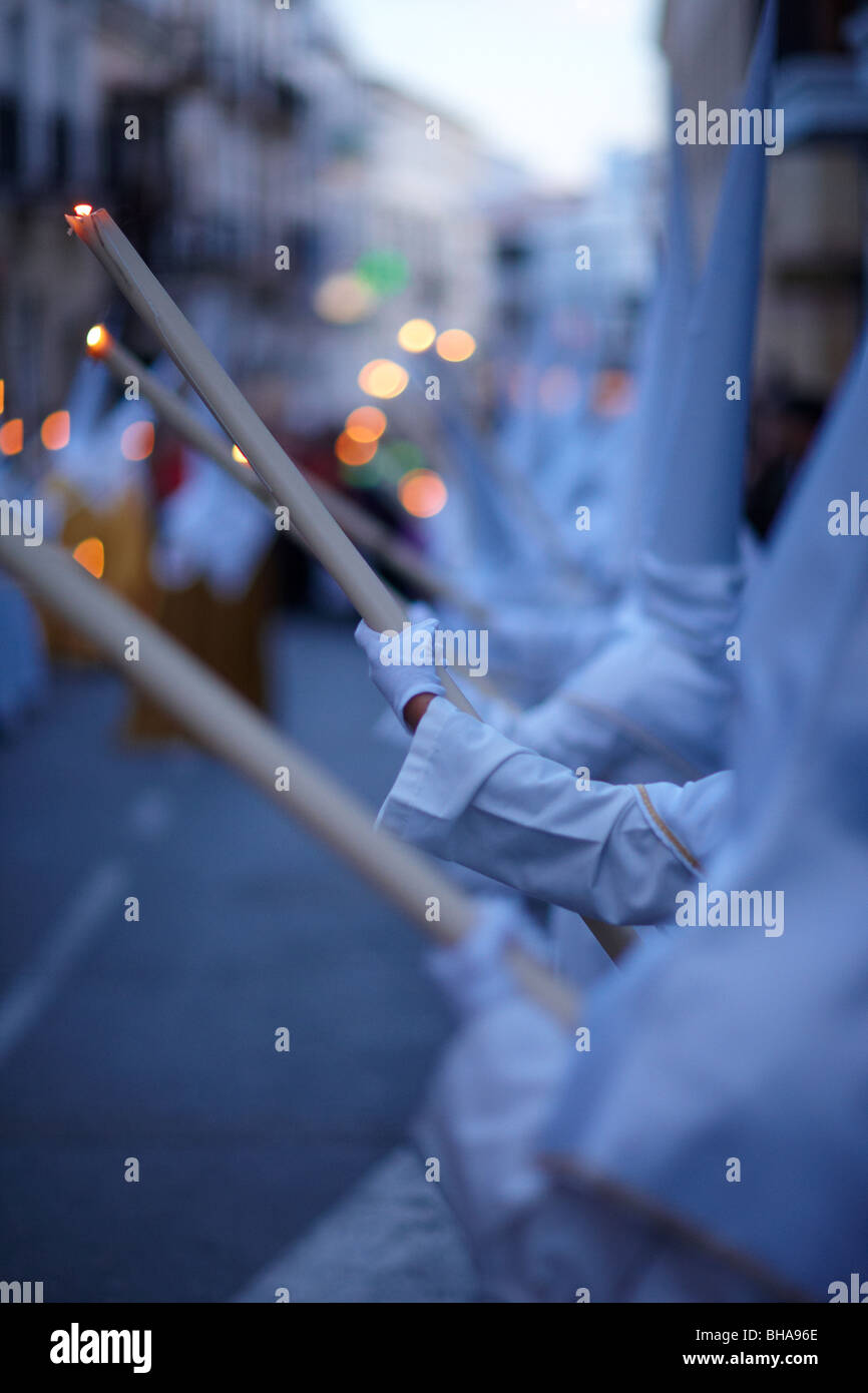 penitents holding candles at dusk in the Semana Santa procession in Vera Malaga, Andalucia, Spain - Stock Image