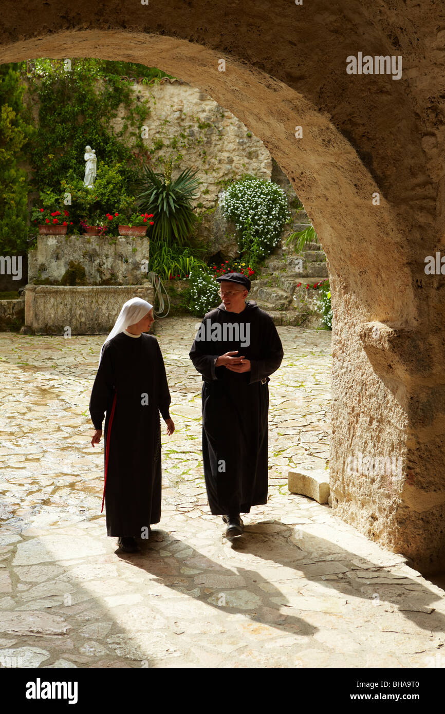 the padre and a nun in the courtyard at St. Eutizio Abbey, nr Preci, Umbria, Italy - Stock Image