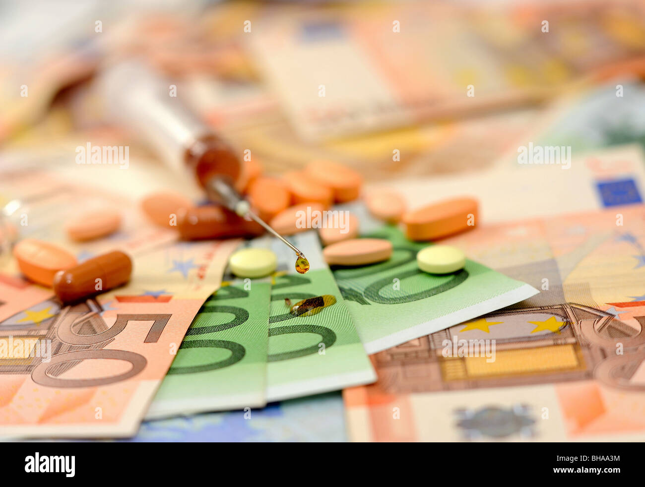 Medicines, a syringe and tablets against paper money - Stock Image