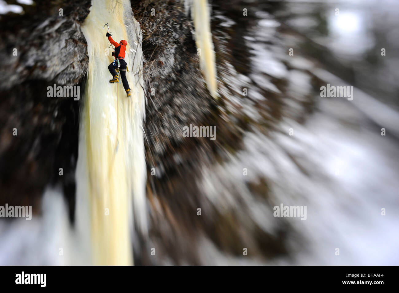 Woman ice climber ascends a large icefall in Southcentral Alaska - Stock Image