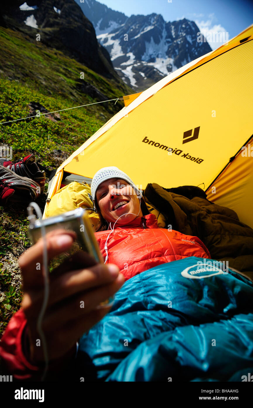 Woman listens to her iPod at camp on the Williwaw Lakes Trail, Chugach State Park, near Anchorage, Southcentral - Stock Image