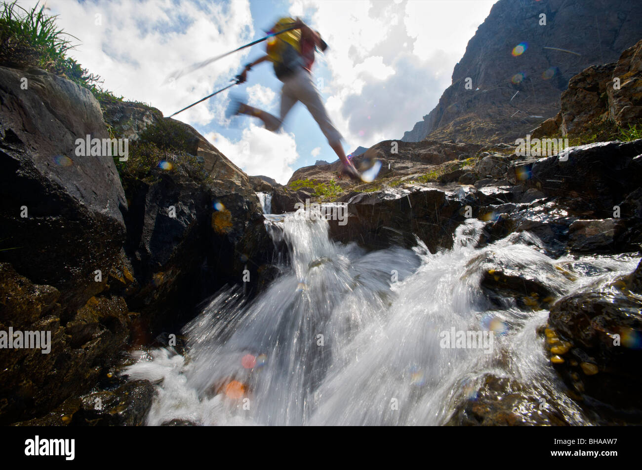 Hiker jumps over a creek on the Williwaw Lakes Trail in Chugach State Park, near Anchorage, Southcentral Alaska, - Stock Image