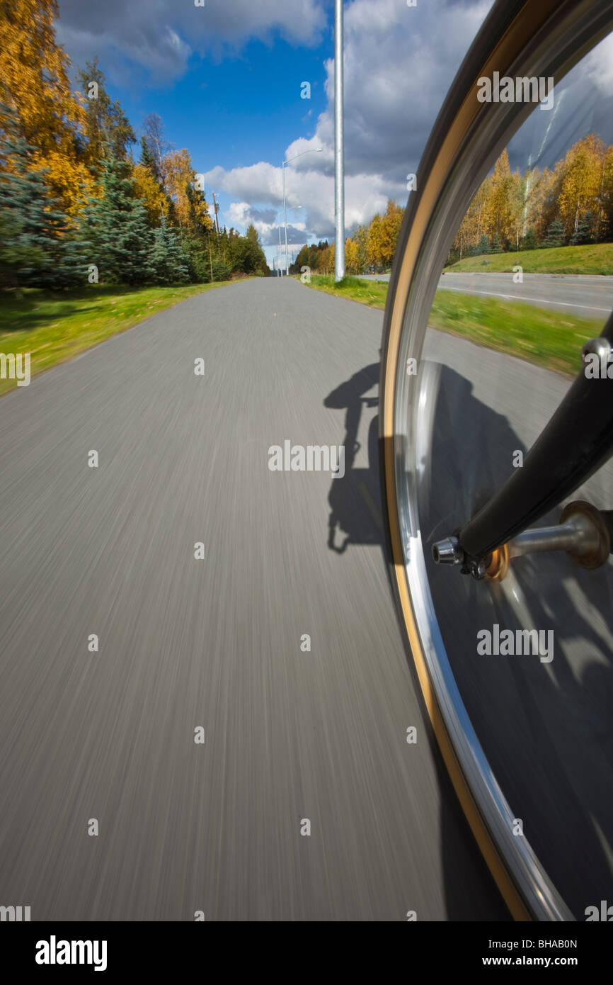 Wide angle view of a biycle tire in motion on a bike path in Anchorage, Southcentral Alaska, Autumn - Stock Image