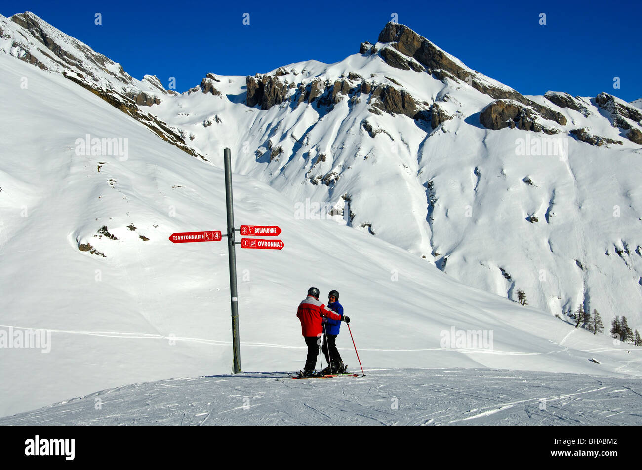 Two skiers standing at a directional sign in the skiing area Ovronnaz, Valais, Switzerland - Stock Image