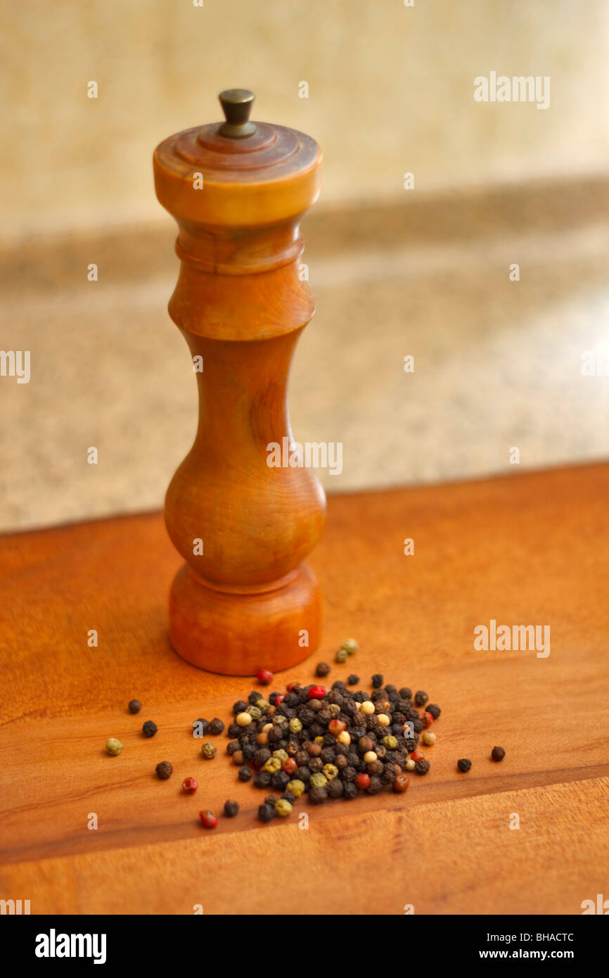 Mixed dried whole peppercorns with a hand turned wooden pepper mill - Stock Image