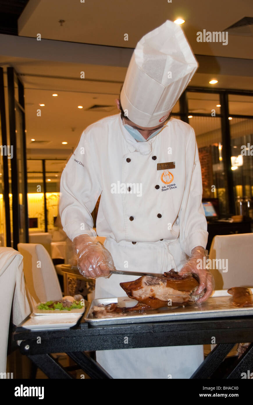 "Beijing, CHINA- ""Da Dong Roast Duck"" ""Peking Duck"" Chinese Restaurant, Chef Carving Meat at Table in Dining Room Stock Photo"