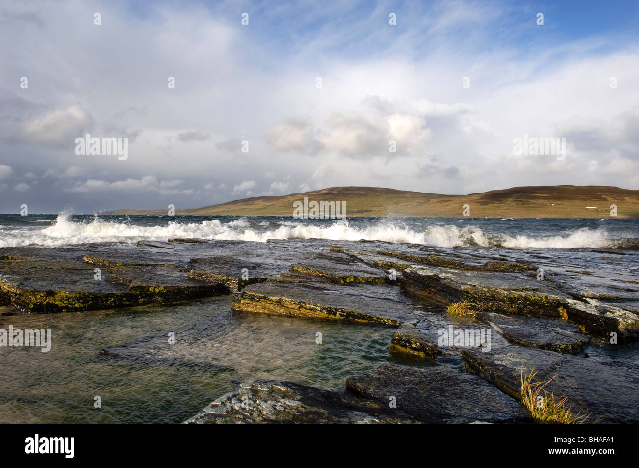 Waves break on the shore at the Brock of Burness looking toward the Island of Rousay,, from the mainland Orkney, - Stock Image
