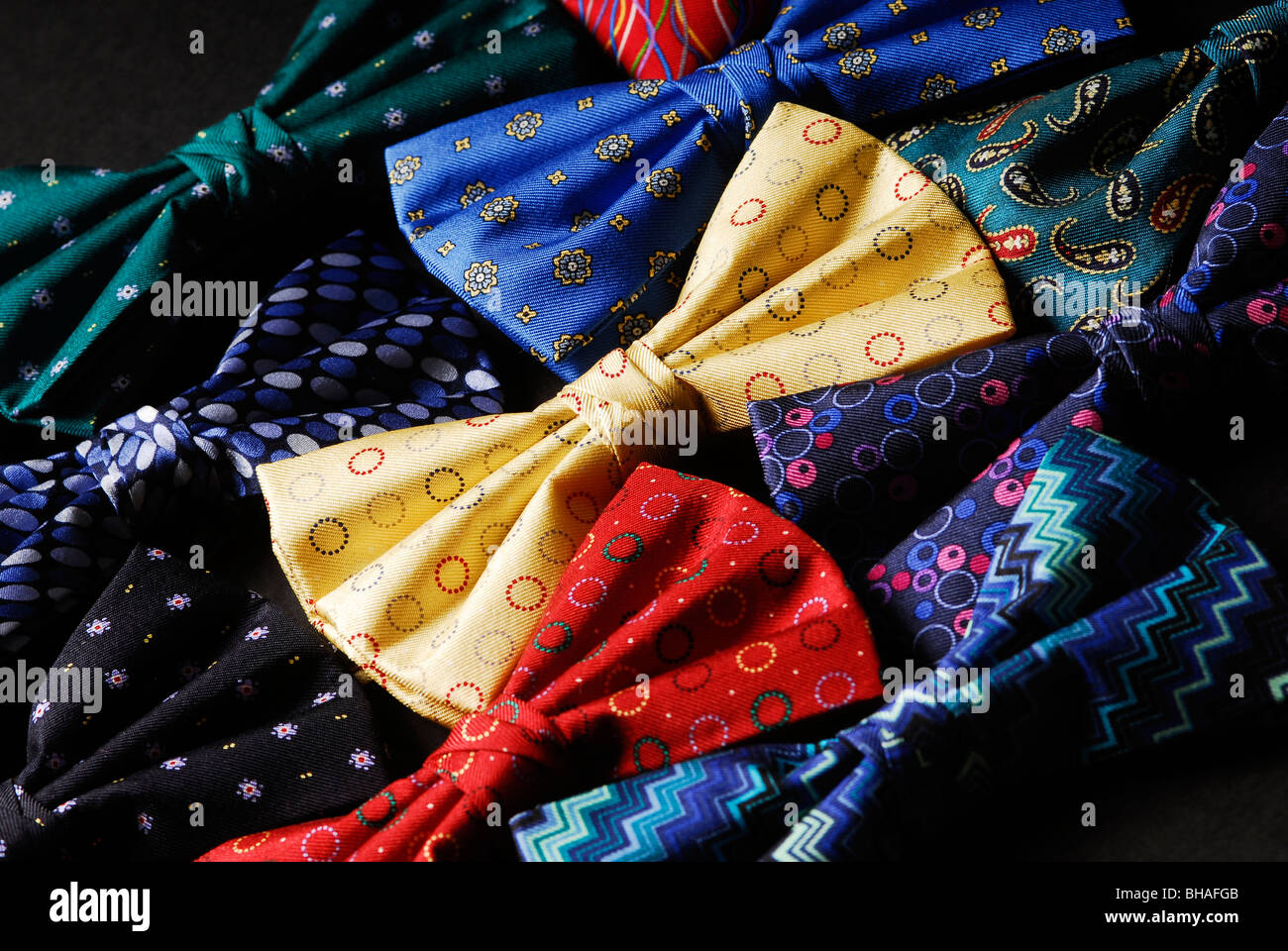 Colourful bow ties on a black background UK - Stock Image
