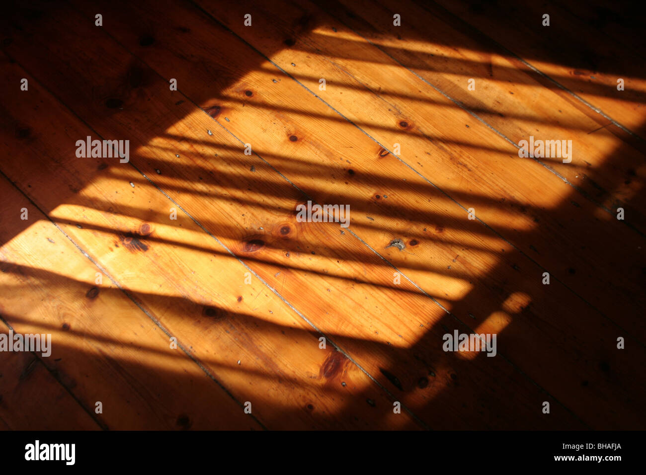 Sunlight falling on wooden polished floorboards, creating shadows. - Stock Image