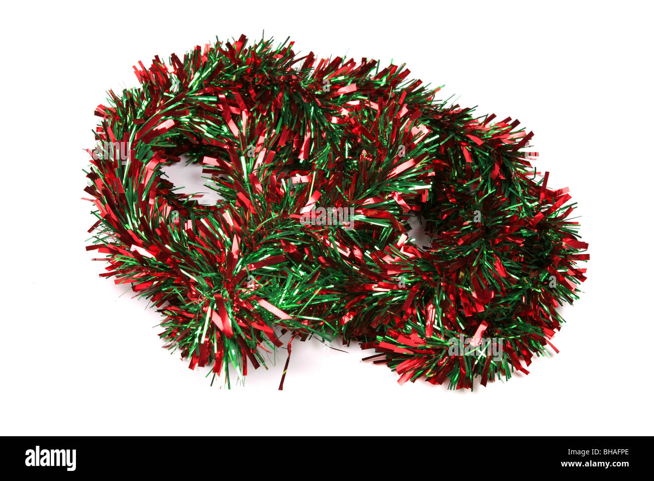 Red and Green Tinsel against a white background - Stock Image