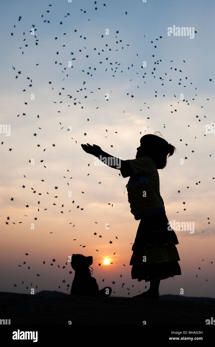 Silhouette of a young Indian girl catching falling stars at sunset. India Stock Photo