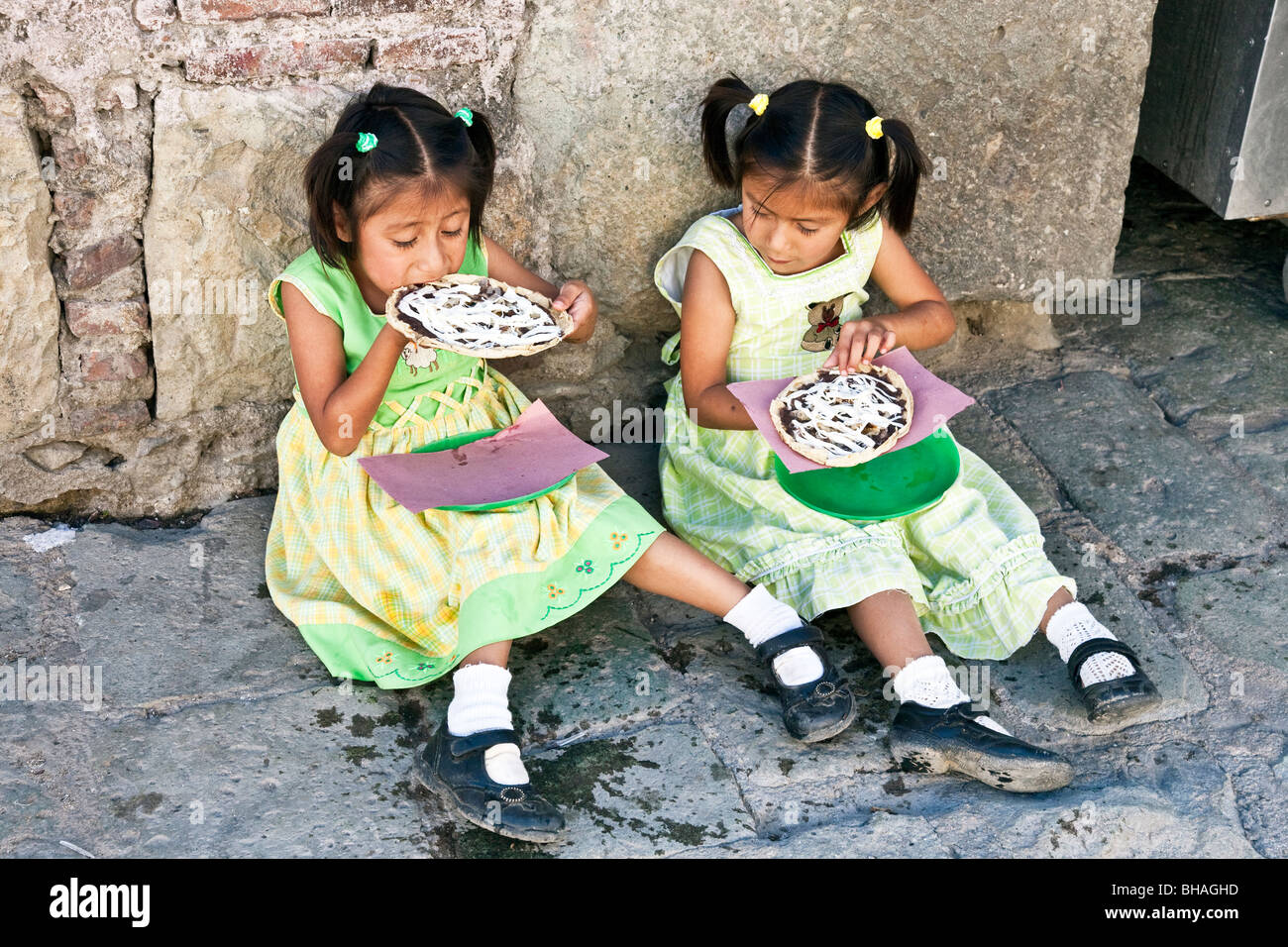 small Mexican twin girls in pretty gingham dresses & scuffed Mary Janes sit on sidewalk & enjoy lunch treats - Stock Image