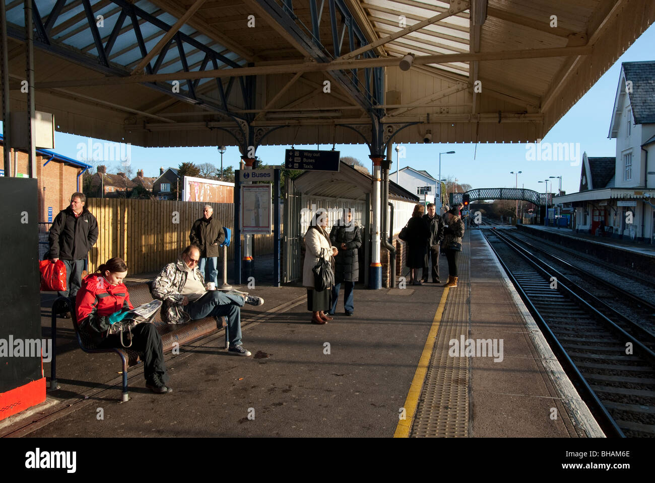 Passengers waiting for train on Petersfield railway station platform - Stock Image