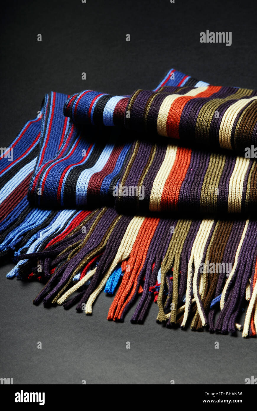 A selection of woolen scarves on a black background UK - Stock Image