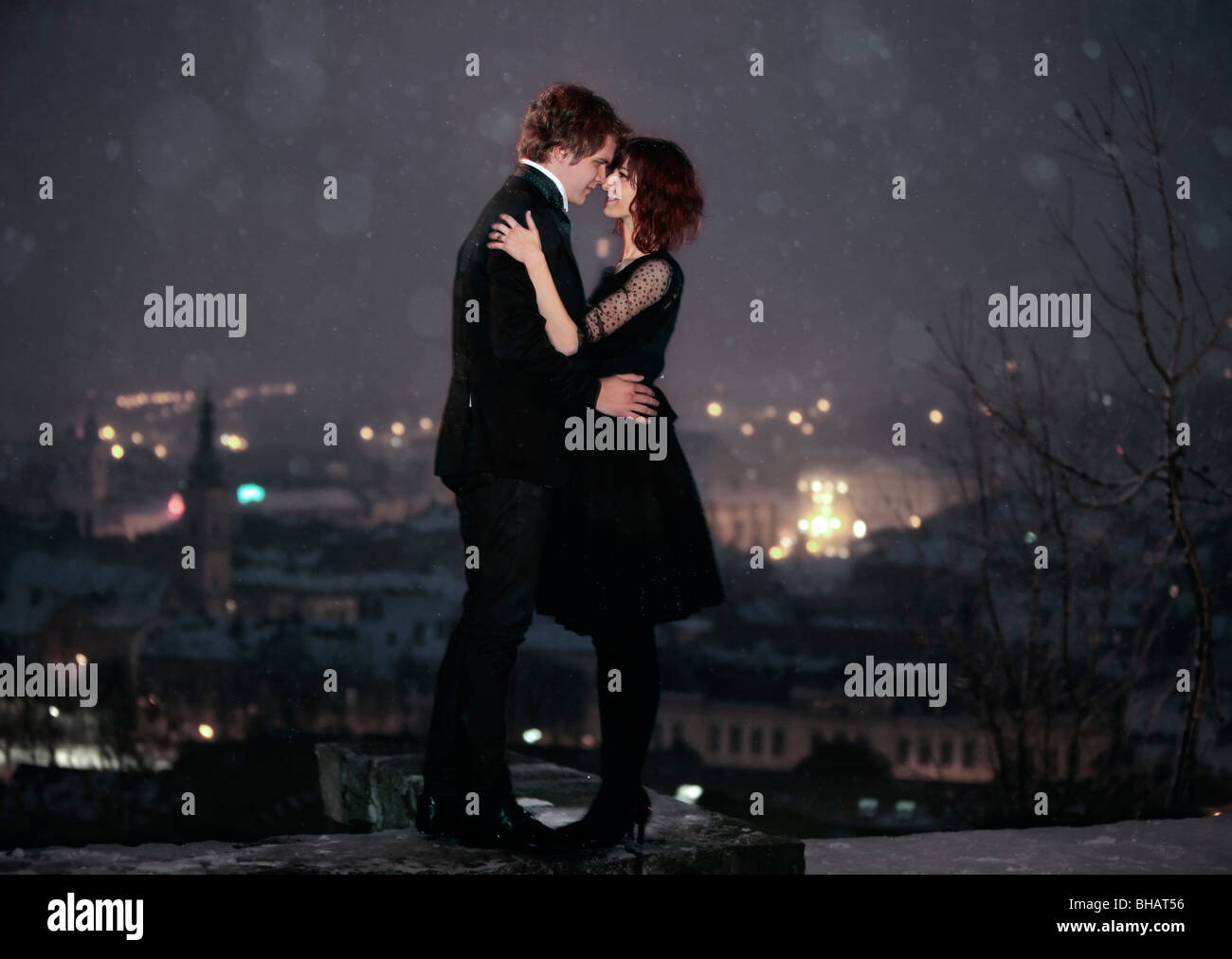 Full length profile of Romantic Couple looking into each others eyes against the city at night on valentine's - Stock Image