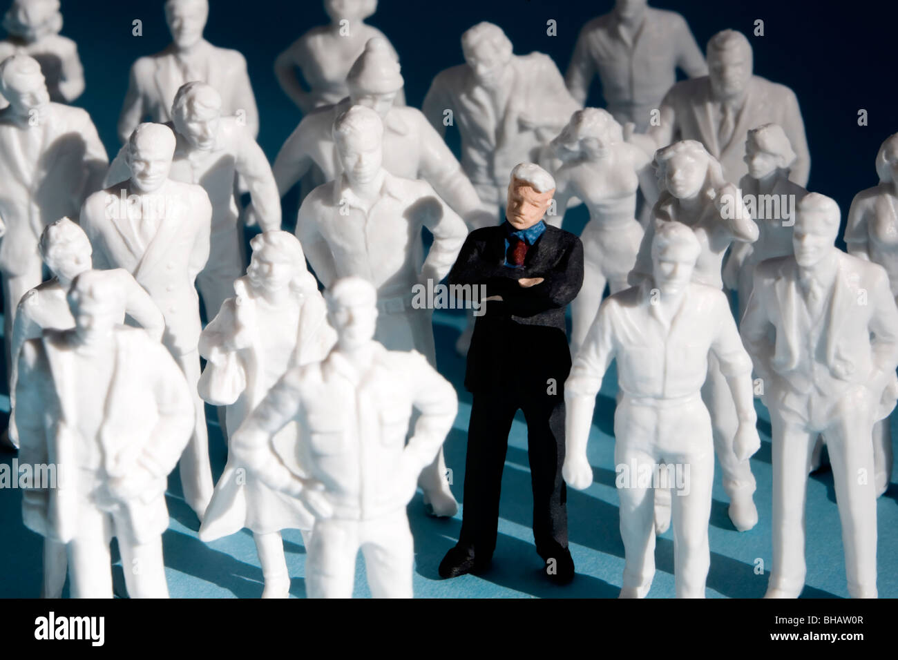 Miniature plastic figures, crowd of people. One figure is painted, surrounded by unpainted white figures. - Stock Image