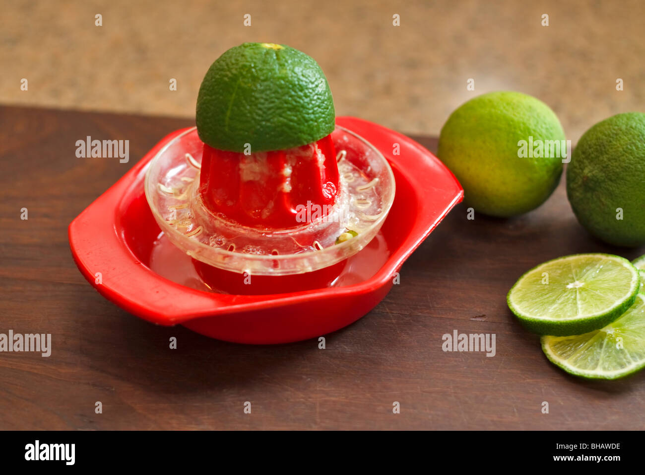 Squeezing limes for juice - Stock Image