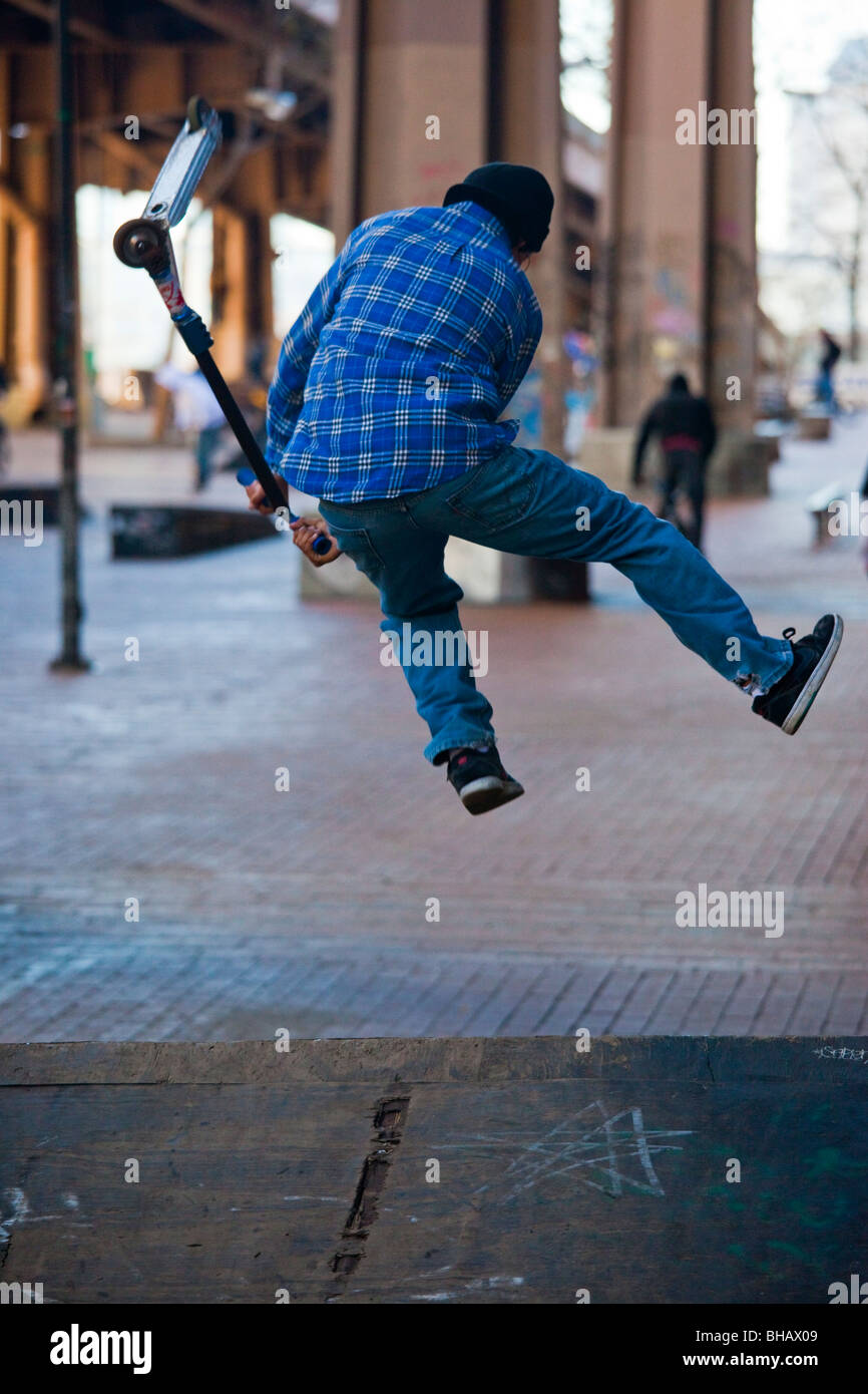 Teen doing razor scooter tricks in Manhattan, New York City Stock Photo