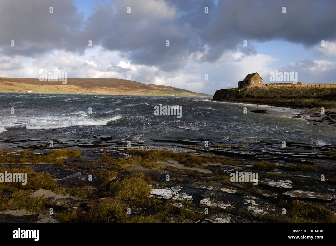 Waves crash over rocks at the Brough of Burness on the mainland, looking towards the Islands of Rousay, Orkney Islands, - Stock Image
