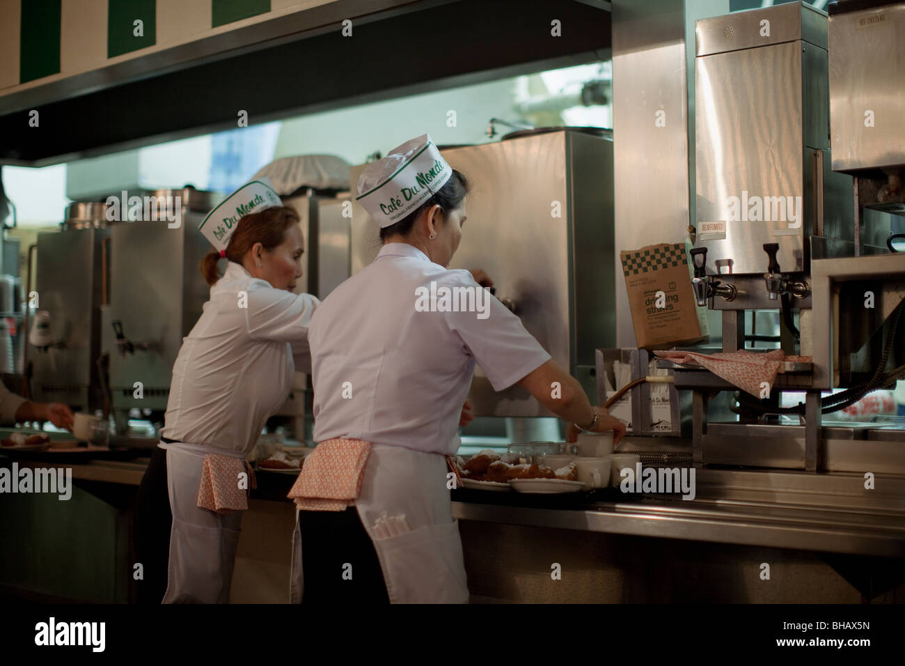 Waitresses at Cafe Du Monde serving up beignets and chicory coffee in the morning. - Stock Image