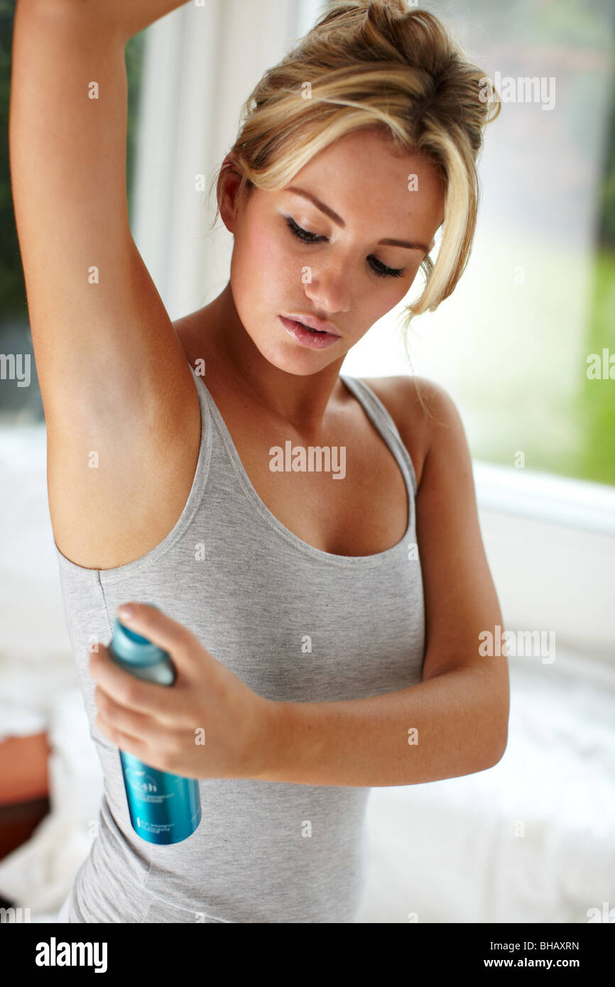 Young girl applying deodorant - Stock Image