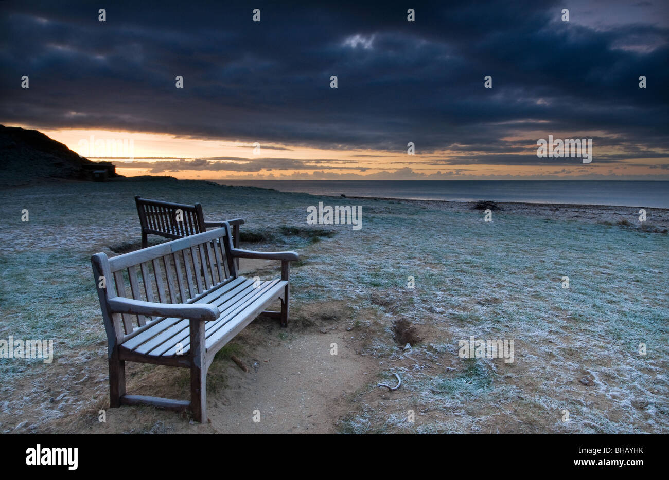 Pair of frosted benches next to beach at Charmouth, Dorset - Stock Image